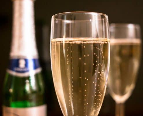 Wie lange hält sich Sekt? - Eine Nahaufnahme von einer Flasche und einem Glas Wein - Champagner